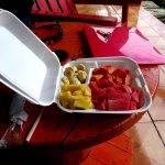 Plato de fruta da asporto: banane, ananas, cocomero, papaya