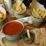 Roasted tomato soup with bread and butter and sides of chips