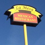 Standing under the La Mesa Sign. It is located right off a busy road across the street fromshops