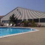 nice size outdoor pool with lots of lounge chairs & grills to cook on