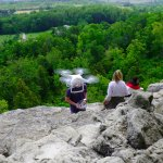 A group of young people doing drone flight testing atop the Niagara escarpment rock cliff.