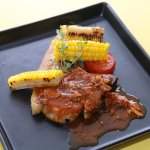 Grilled juicy and tender pork chop with brown bacon sauce and some grilled corn