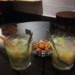 2 caipirinhas con frutos secos y chuches que te sirven de acompañamiento.