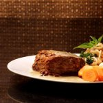 Grilled beef steak with vegetables and spicy noodles
