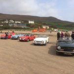 Triumph TR owners and their vehicles on the beach