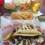 Fish tacos, fries and a beer with burger in the background.