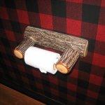 Plaid wallpaper and quaint toilet paper holder.