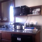 minibar/sink in room with fridge, coffee maker with coffee, microwave w/ popcorn and bottle of w