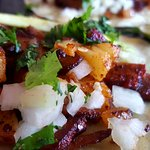 Tacos al pastor, done street style, in achiote with roasted pineapple