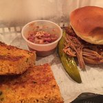 Pulled pork sandwich with red beans and rice and cornbread