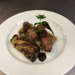 Lamb tenderloin served with wild greens wrapped in grilled eggplant & garnished