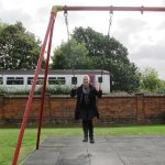 Me on the swings with train passing in background.