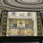 Mirror shows ornate ceiling against contrasting floor tiles