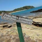 Aviso de pedra escorregadia no caminho de pedras que adentra a praia