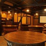 杉樽を使用したテーブルが並ぶ、ムード溢れる長久BAR。こちらでは日本酒造りについての映像をご覧頂けます。