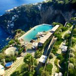Infinity pool on the edge of the almost vertical cliff, between sky and sea