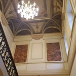 Above the red carpet staircase, guests can enjoy a wonderful painted ceiling
