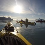 Cool shot looking out the front of the kayak with our whole crew and some icebergs.
