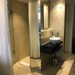 La ducha tras una mampara y una cortina que la separa de la habitación