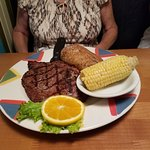 Ribeye with baked potato and corn on the cob.