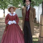 Reenactors. The renovation is behind the barrier behind them.