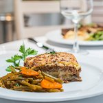 Traditional Moussaka casserole dish with layers of eggplant, ground lamb, béchamel sauce