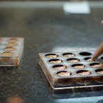 chocolatier filling chocolate ganache molds with salted caramel