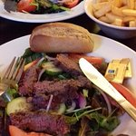 Tender steak on a bed of salad with bread roll and chips.