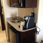 Frig, coffee maker and microwave in room.