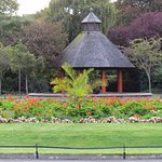 Gazebo surrounded by colorful flowers and trees