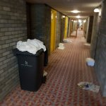 Piles of used bedding and uneaten food on trays left for hours in the 4th floor corridor..