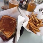 Reuben sandwich and fries with a side of tartar sauce and Whistling Pig Beer