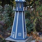 Lighthouse in garden near parking lot in back of restaurant