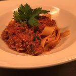 Pappardelle pasta in a rich meaty tomato ragú Bolognese style tossed with parmesan cheese