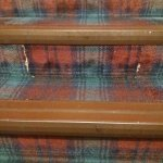 Carpet torn and worn on the stairways.
