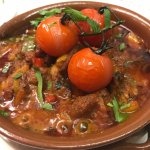 Slow cooked lamb casserole presented in a clay pot.