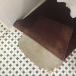 Bathroom floor covered by a grotty mat and missing tiles