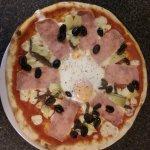 pizza capricciosa, with tomato, mozzarella, ham anchovies, artichoke, olive and egg