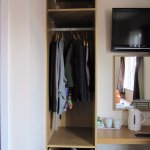 room has 1 open front wardrobe unit with 7 hangers, twin beds, 1 chair, TV