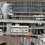 Construction of neighbouring building. Crane horns, trucks reversing, pylons being driven down e