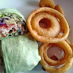 Spinach veggie wrap with onion rings on side.
