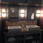 Décoration soignée pour la salle de bain avec ses deux lavabos.