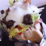 Shawarma de carne en pan pita con cebolla, tomate y lechuga, acompañado de salsa de yoghurt.