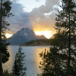 The sunset is dramatically golden behind Mount Moran