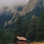 Nestled beneath the misty Flatirons, there is a small hut. All who enter, leave something behind