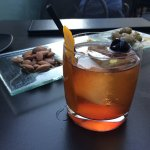 Spiced bourbon old fashioned and complimentary bar snacks at the rooftop lounge.