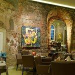 rustikale Mauern mit Bildern und schräggestelltem Spiegel.