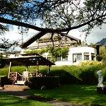Gartenanlage mit Pavillon, dahinter das Hotel