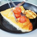 Saganaki Kefalograviera – grilled Greek cheese served with roasted cherry tomatoes, lemon and ol