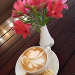 Cappuccino with biscuits and fresh flowers on tables.